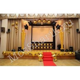 Оформление сцены золотыми шарами и гирляндами